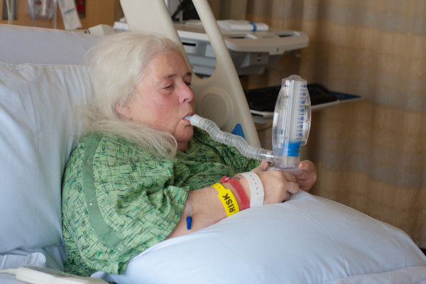 Woman suffering in bed with CPOD using a spirometer