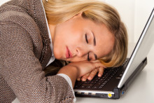 woman exhausted at her laptop