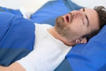 Man snoring and showing one possible sleep apnea symptom